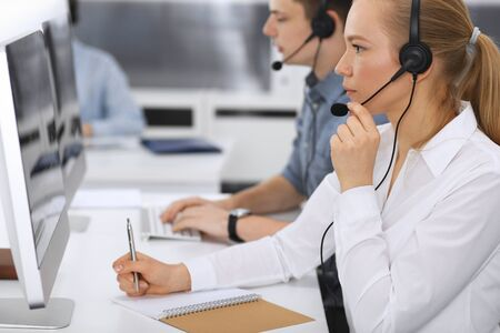 Call center. Group of casual dressed operators at work. Focus on business woman in headset at customer service office. Telesales in business
