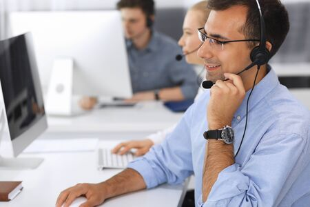 Call center. Group of casual dressed operators at work. Focus on adult businessman in headset at customer service office. Telesales in business
