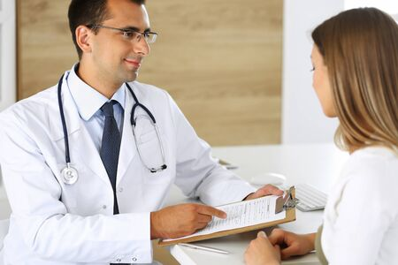 Doctor and patient discussing the results of a physical examination while sitting at a desk in a clinic. A male doctor using a clipboard to fill out a medical history of a young womans medication. Medical and Healthcare Concepts