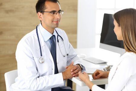 Doctor and patient discussing the results of a physical examination while sitting at a desk in a clinic. Medicine and Healthcare Concepts Banco de Imagens