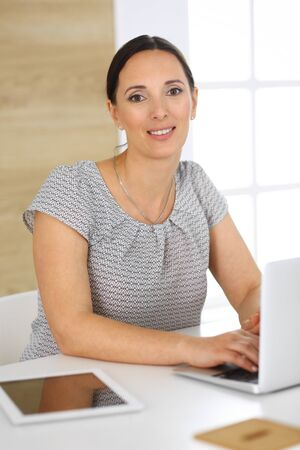 Cheerful smiling business woman working with laptop computer while sitting at the desk in modern office. Middle aged female lawyer or auditor at work. Business people concept