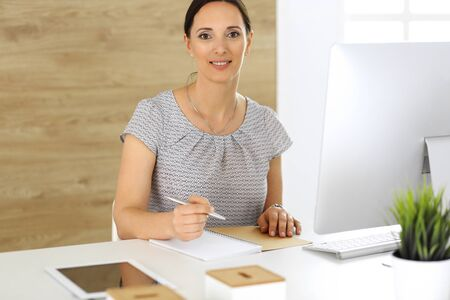 Cheerful smiling business woman working with pc computer while sitting at the desk in modern office. Middle aged female lawyer or auditor at work. Business people concept