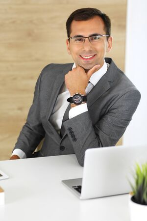 Cheerful smiling businessman sitting at a desk in modern office. Headshot of male entrepreneur or company director at workplace. Business concept Banco de Imagens