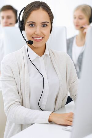 Call center. Group of operators at work. Focus on beautiful woman receptionist in headset at customer service white colored office. Business concept