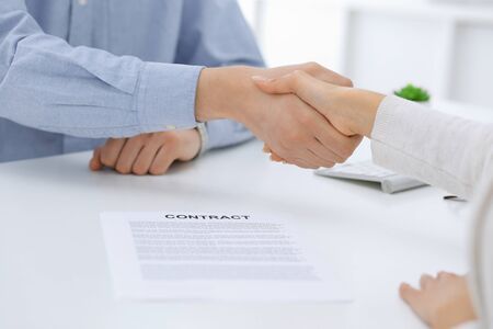 Business people shaking hands at meeting or negotiation after contract discussing. Businessman and woman handshake at office while sitting at the desk. Success concept