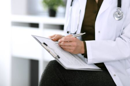 Woman doctor writing something at clipboard while sitting at the chair, close-up. Therapist at work filling up medication history records. Medicine and healthcare concept