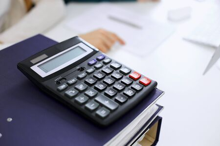Calculator and binders with papers are waiting to be processed by business woman or bookkeeper working at the desk in office back in blur. Internal Audit and tax concept