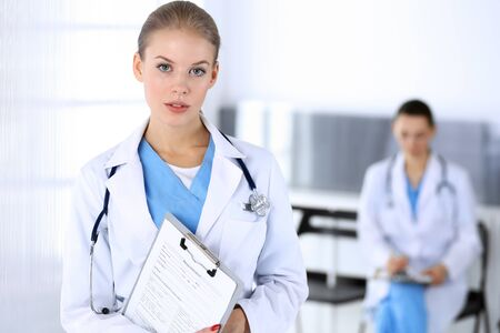 Doctor woman standing in emergency hospital office with colleague at background. Physician at work, studio portrait. Medicine and health care concept