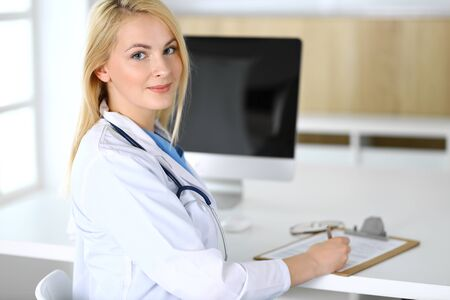 Doctor woman at work while sitting at the desk in hospital or clinic. Blonde cheerful physician ready to help patients. Data and best service in medicine and healthcare