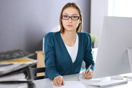 Accountant checking financial statement or counting by calculator income for tax form, hands close-up. Business woman sitting and working at the desk in office. Audit concept