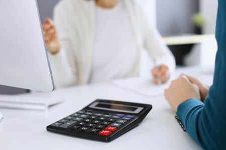 Accountant checking financial statement or counting by calculator income for tax form, hands close-up. Business woman sitting and working with colleague at the desk in office. Audit concept