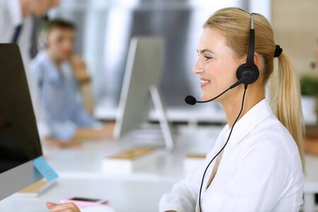 Blonde business woman using headset for communication and consulting people at customer service office. Call center. Group of operators at work at the background.