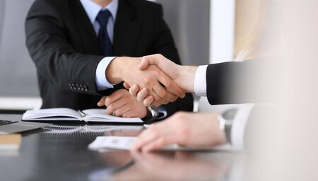 Businessman shaking hands with his colleague or partner above the glass desk in modern office, close-up. Unknown business people at meeting. Teamwork, partnership and handshake concept.