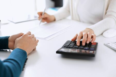 Accountant checking financial statement or counting by calculator income for tax form, hands closeup. Business woman sitting and working with colleague at the desk in office. Tax and Audit concept.