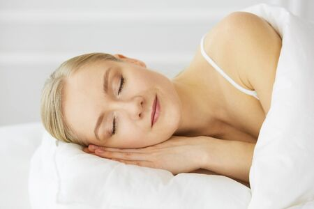 Beautiful young woman sleeping in bedroom comfortably and blissfully. Waking up in fairy morning