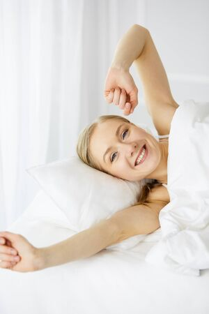 Smiling woman stretching hands in bed after waking up, entering a day happy and relaxed after good night sleep. Sweet dreams, fairy morning concept 版權商用圖片