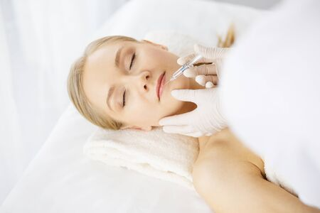 Beautician doctor doing beauty procedure with syringe to caucasian female face. Cosmetic medicine and surgery, beauty injections concept