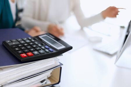 Calculator and binders with papers are waiting to be processed by business woman or bookkeeper working at the desk in office back in blur. Internal Tax and Audit concept.