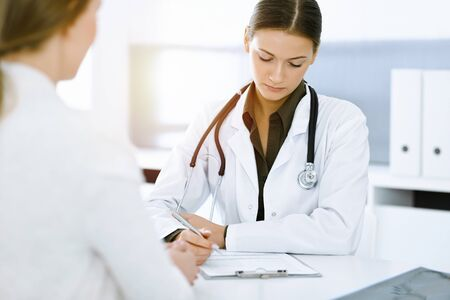 Woman-doctor and patient sitting and talking at sunny hospital office. Green color blouse suits to therapist. Medicine concept Standard-Bild
