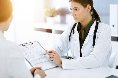 Woman-doctor and patient sitting and talking at sunny hospital office. Green color blouse suits to therapist. Medicine concept