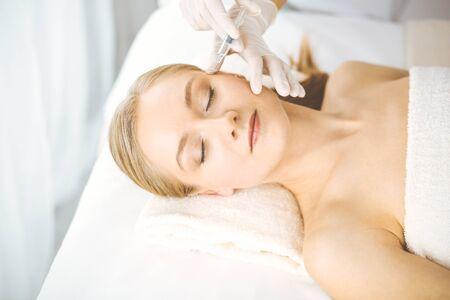 Beautician doctor doing beauty procedure with syringe to blonde female face. Cosmetic medicine, beauty injections concept