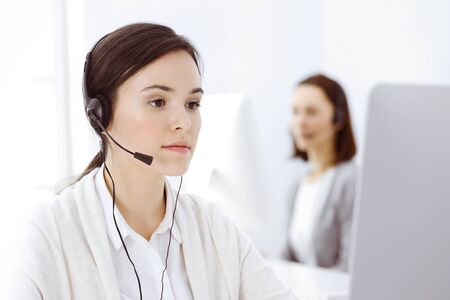 Call center. Casual dressed woman sitting in headset at customer service office. Group of operators at work. Business concept Фото со стока