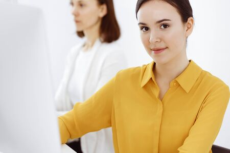 Businesswoman in mustard colored blouse looking at camera at office, headshot