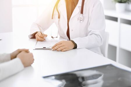 Unknown woman-doctor and female patient sitting and talking at medical examination in sunny clinic, close-up. Therapist filling up medication history record. Medicine concept Foto de archivo