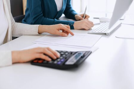 Accountant checking financial statement or counting by calculator income for tax form, hands closeup. Business woman sitting and working with colleague at the desk in office toned in blue. Tax and Audit concept