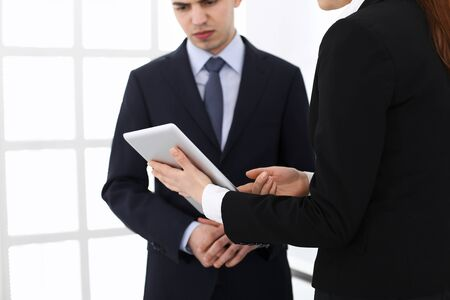 Businessman and woman using tablet computer for discussing questions in office. Partners or colleagues at meeting. Business cooperation concept