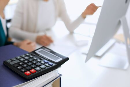 Calculator and binders with papers are waiting to be processed by business woman or bookkeeper working at the desk in office back in blur. Internal Tax and Audit concept