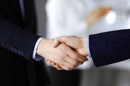 Business people shaking hands at meeting or negotiation, close-up. Group of unknown businessmen and a woman standing in a modern office. Teamwork, partnership and handshake concept Foto de archivo