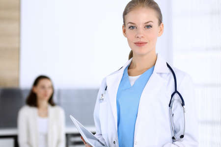 Doctor woman filling up medication history record while standing in emergency hospital office with patient in queue at background. Physician at work, portrait shoot. Medicine and health care concept