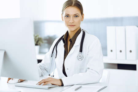 Woman-doctor typing on pc computer while sitting at the desk in hospital office. Data in medicine and healthcare Фото со стока