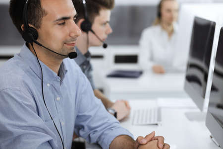 Call center. Group of casual dressed operators at work. Adult businessman in headset at customer service office. Telesales in business