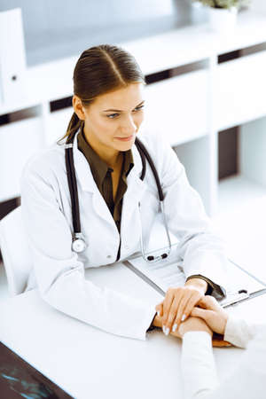 Woman doctor reassuring her female patient at hospital office. Medical ethics, human support and trust concept in healthcare Standard-Bild