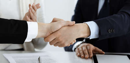 Business people shaking hands after contract signing in modern office. Teamwork and handshake concept