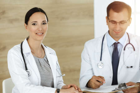 Two doctors discussing treatment problems while sitting at the desk in sunny office