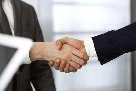 Unknown diverse business people are shaking hands finishing contract signing, close-up. Business and handshake concept Banco de Imagens