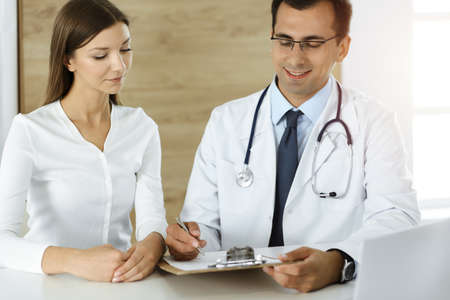 Doctor and patient discussing medical exam results while sitting at the desk in sunny clinic