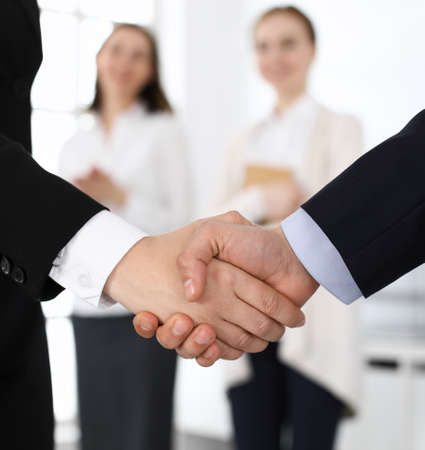 Businessman and woman shaking hands with colleagues at the background. Handshake at meeting in office. Concept of success in business