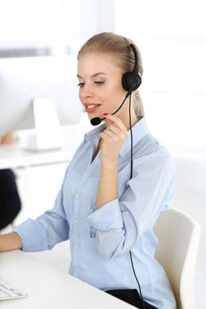 Blond woman call operator is using computer and headset for consulting clients online. Group of diverse people working as customer service occupation. Business concept