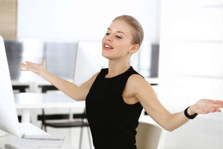 Young blond businesswoman working on computer while sitting at the desk in modern office. Business people concept. Black dress do suits to her much at this portrait