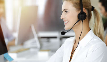 Blond business woman using headset for communication and consulting people at sunny office. Call center
