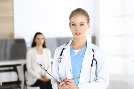 Woman - doctor is using clipboard for filling up medication history record form in clinic at the background of patient. Medicine concept