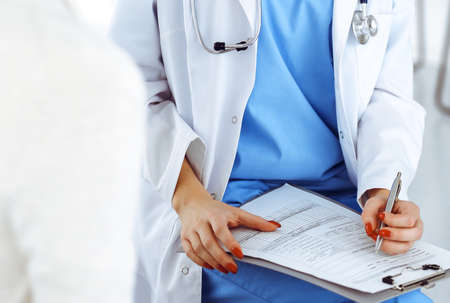 Woman - doctor consults her female patient while using clipboard and medication history record. Medicine concept