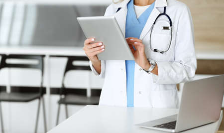 Unknown woman-doctor at work in clinic. Female physician using tablet computer, close-up. Medicine concept