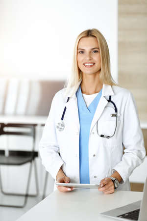 Woman-doctor controls medication history records and exam results while using tablet computer in sunny hospital. Medicine and healthcare concept
