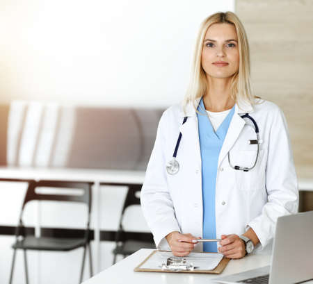 Woman-doctor at work in clinic happy of her profession. Blond female physician controls medication history record and medical exam results. Medicine concept Stok Fotoğraf
