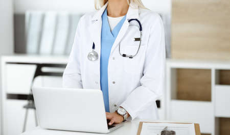 Unknown female physician using laptop computer, close-up. Woman-doctor at work in clinic. Medicine concept